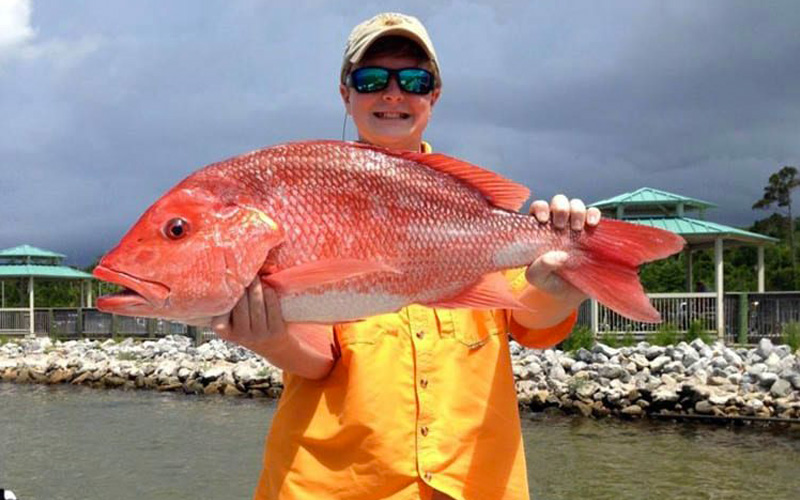 Kid wearing sunglasses holding red snapper